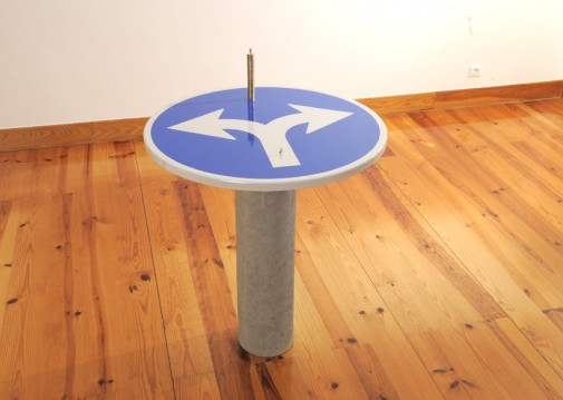 """This Way Only # 3"", 2008, Traffic sign, cement drain-pipe, coins and model figures, 103 x 74 x 74 cm"